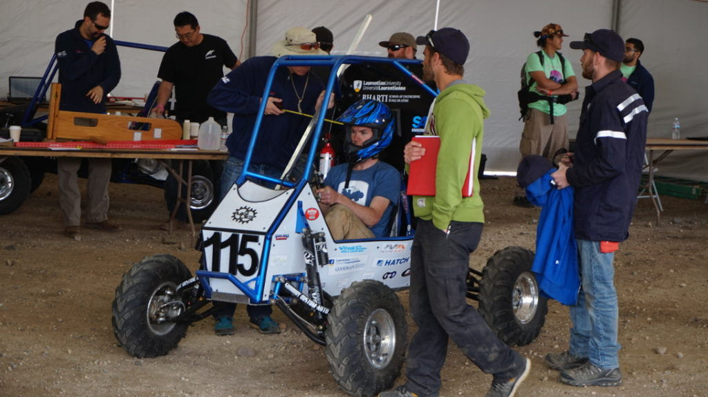 The distances from Justin's helmet to the roll cage are checked for compliance with the SAE Baja rule book.